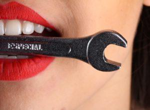 Гаечный ключ во рту девушки