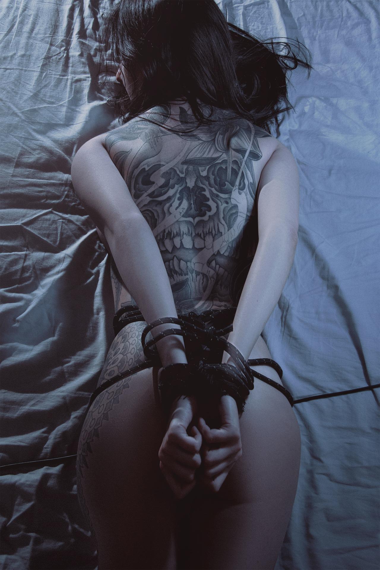 Связанная девушка с татуировкой на спине