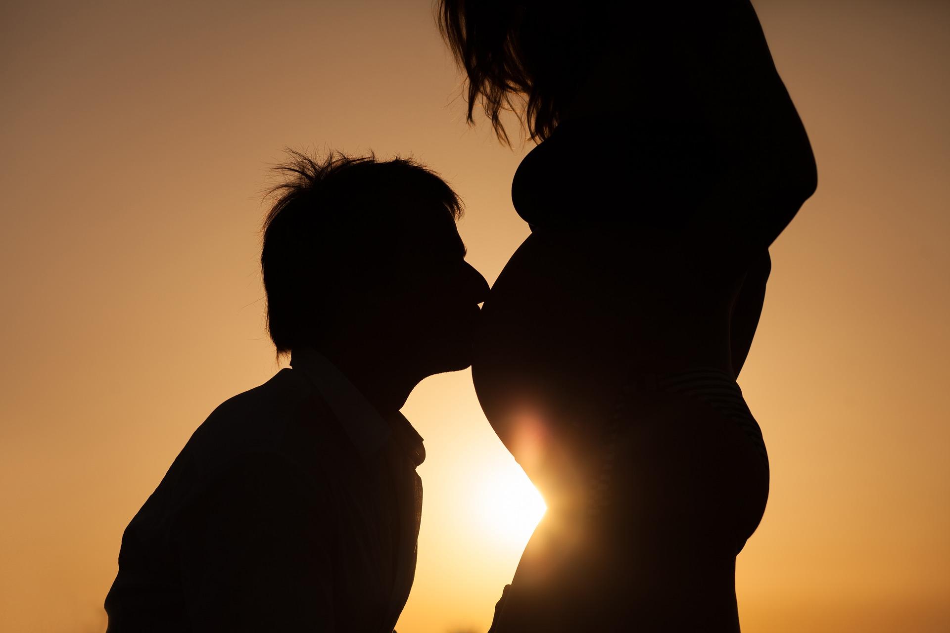 Мужчина целует живот беременной женщины