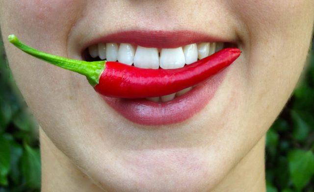 Девушка зажимает в зубах острый перец