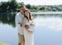 Беременная женщина с мужем на берегу водоема